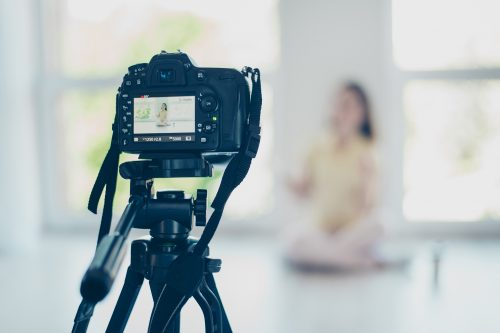 Focused view of video camera, recording pretty brunette girl blogger, talking, sitting at the floor with crossed legs in a casual outfit in light modern white studio
